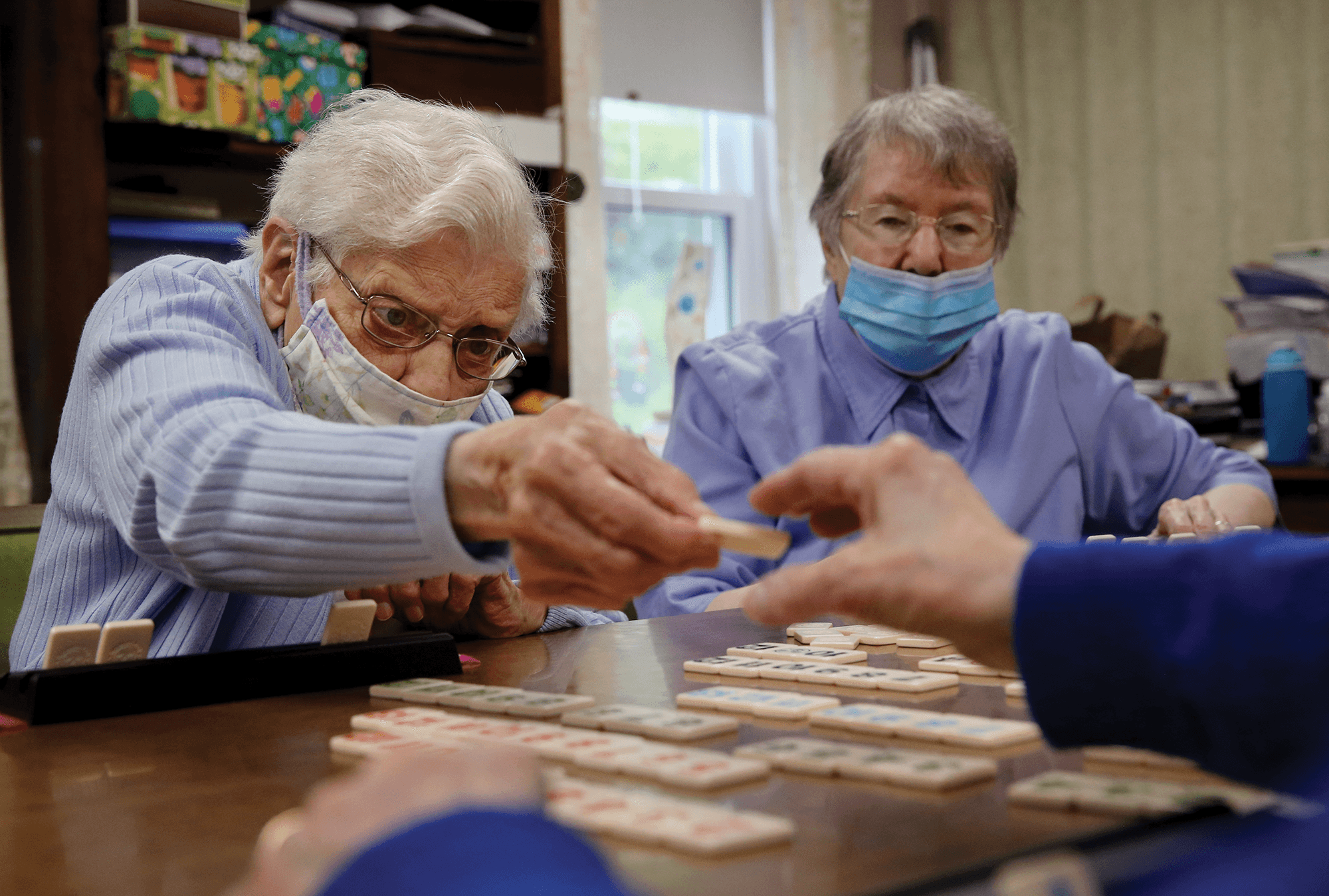 Three Felician Catholic sisters play a board game together, all wearing masks.