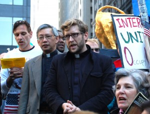 The Rev. Michael Ellick (center in black) leads a multi-faith service in Zuccotti Park on Sunday. Photo by Cathleen Falsani/Sojourners