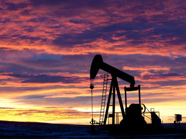 A pumpjack retrieves oil from the group against a sunset background