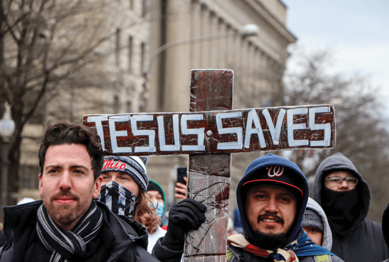 Trump supporters at the Jan. 6 Capitol riot hold a cross that says 'Jesus Saves'