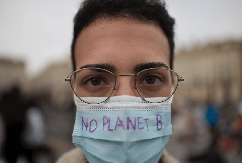 """A young adult with dark hair and glasses is wearing a mask with the words """"No Planet B"""" written on it."""