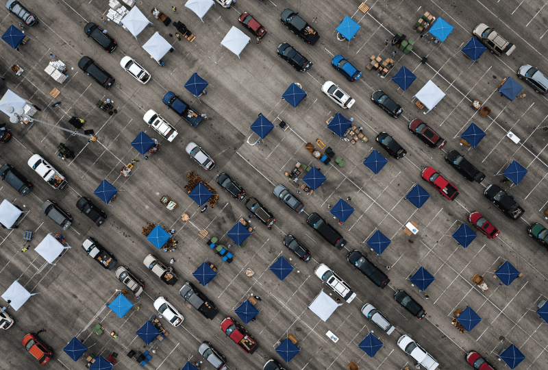 Aerial view of cars waiting in a food line in a parking lot in Texas.