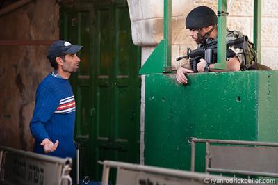 A Palestinian man is questioned at an Israeli military checkpoint.