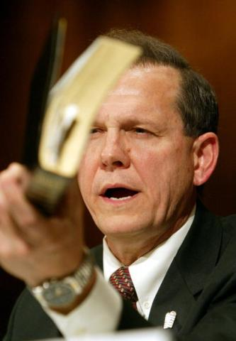 Justice Roy Moore holds a Bible while testifying in a hearing. Via Getty Images.