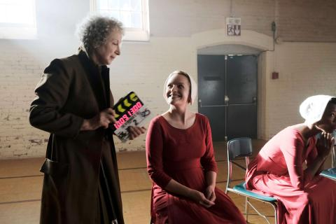 Margaret Atwood holds a slate while laughing with Elizabeth Moss during filming of The Handmaid's Tale series.