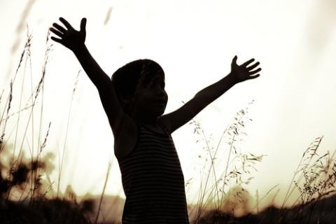 Young boy reaches to the sky. Photo courtesy Zurijeta/shutterstock.com