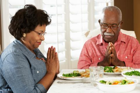 Couple praying at mealtime, Monkey Business Images / Shutterstock.com