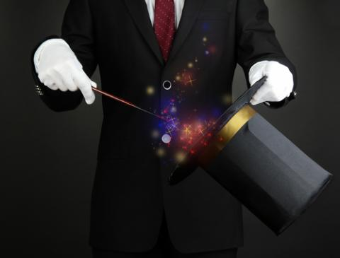 Magician performing on dark background, Africa Studio / Shutterstock.com
