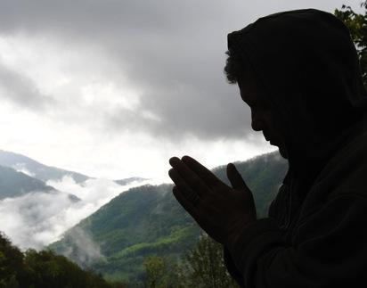 A figure prays while a storm rolls in. Image courtesy Waddell Images/shutterstoc