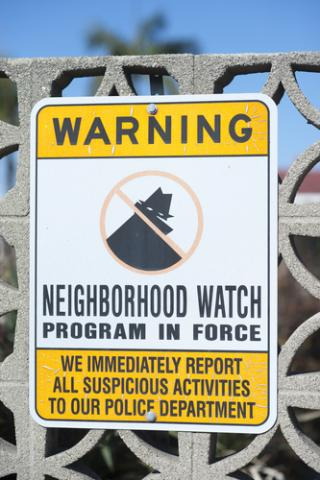 Neighborhood watch sign on a gate. Photo courtesy gabriel12/shutterstock.com