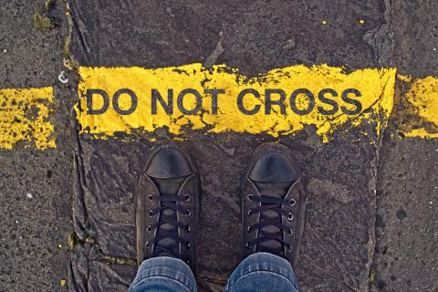 "Sneakers on asphalt road and ""Do Not Cross"" sign. Image courtesy igor.stevanovic"