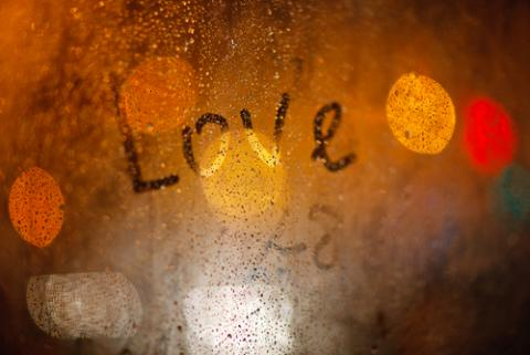 'Love' written on window in the rain, Wolf__ / Shutterstock.com
