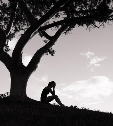 A figure weeps under a tree. Image courtesy KieferPix/shutterstock.com