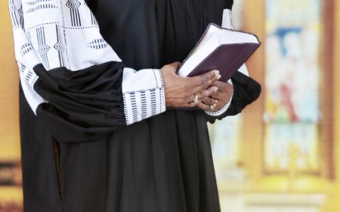 Female clergy holding a Bible, glenda / Shutterstock.com