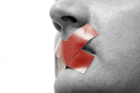 Red tape over mouth photo, Stefan Redel / Shutterstock.com