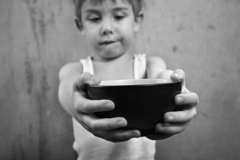 Child holding empty bowl, Suzanne Tucker / Shutterstock.com