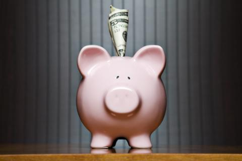 Piggy bank with money sticking out, Kinetic Imagery / Shutterstock.com