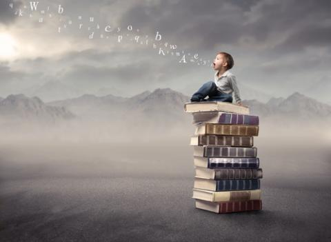 Photo: Child sitting on stack of books, olly / Shutterstock.com