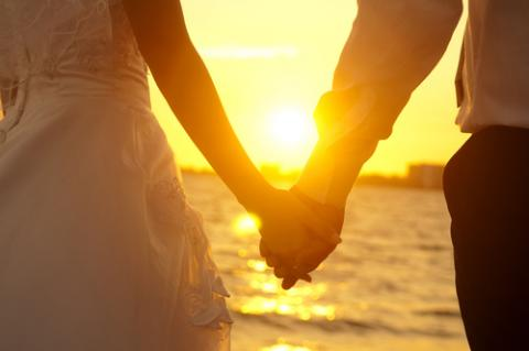 Bride and groom on beach, szefei / Shutterstock.com
