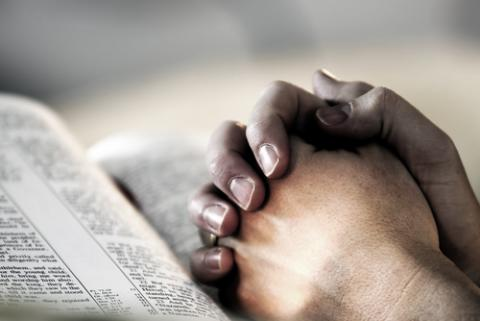 Photo: Hands clasped in prayer. Lincoln Rogers / Shutterstock.com