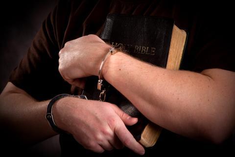 Prisoner clutch Bible, Steven Frame, Shutterstock.com