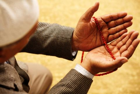 Hands with Muslim prayer beads, Omer N Raja / Shutterstock.com