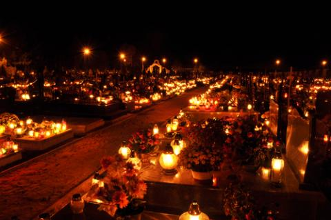Candles illuminate a cemetery on All Saints' Day, wawritto / Shutterstock.com