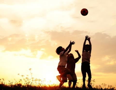 Children playing with a ball at sunset. Image courtesy Zurijeta/shutterstock.com