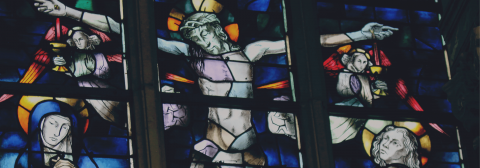 a stained glass window depict Jesus on the cross.