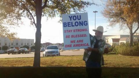 A man in a cowboy hat holds a sign of support outside of a mosque in Irving, Tx