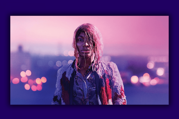 A scene from 'I May Destroy You' features a woman with pink hair looking into the camera frame with a pink sky behind her.