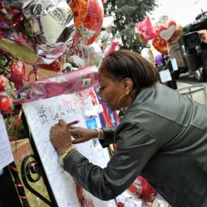 Fan signs a poster for singer Whitney Houston at the New Hope Baptist Church, Ne