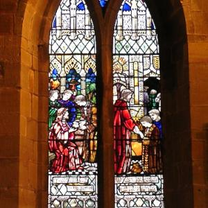 Stained glass church window depicting the Parable of the Talents from Matthew 25