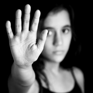 A woman holds up her hand. Image courtesy Kamira/shutterstock.com