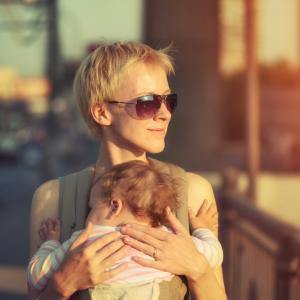 A mother carries her child through a city. Image via Konstantin Sutyagin/shutter