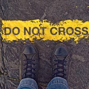 "Sneakers on asphalt road and ""Do Not Cross"" sign. Image courtesy igor.stevanovic"