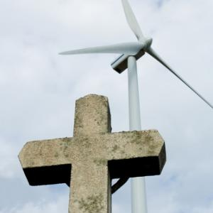Cross in front of a wind farm, BESTWEB / Shutterstock.com