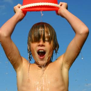 A child dumps ice water over his head. Image courtesy Suzanne Tucker/shutterstoc