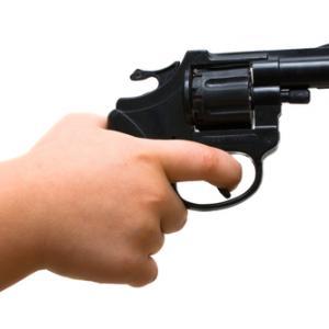 A child points a gun. Image courtesy Marek H./shutterstock.com
