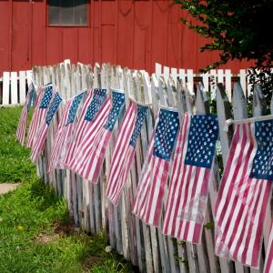 Flag decorated white picket fence, Bill Fehr / Shutterstock.com