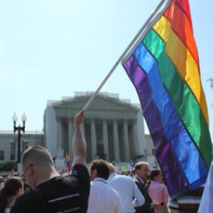 A man holds a gay pride flag in front of the Supreme Court. Photo via Adelle M.
