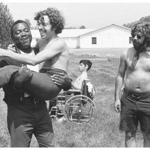 """In a scene from the documentary """"Crip Camp,"""" a camp counselor is carrying a man who is Disabled. Both are laughing."""