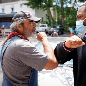 "A Black man and a white man ""high-fiving"" each other with their elbows."