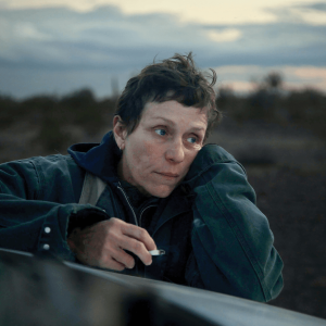 A scene from Nomadland features a woman leaning on the hood of her car.