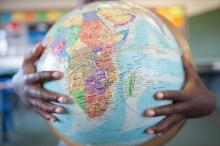 Boys hands hugging globe in classroom / Getty Images