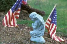 Close-up of a statue and an American flag, Purestock / Getty Images
