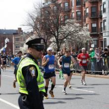 A Police officer stands by as runners pass during the 2013 Boston Marathon. Phot