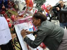 Fan signs a poster for singer Whitney Houston at the New Hope Baptist Church, Ne