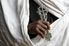 Hand holding Coptic cross.