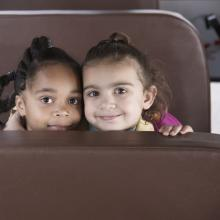 Two young girls on a bus. Image courtesy Blend Images/shutterstock.com.